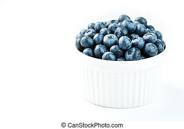 Blueberries in a white Cup on a white background. Isolate, ...