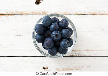 Blueberries in crystal bowl on white wooden background