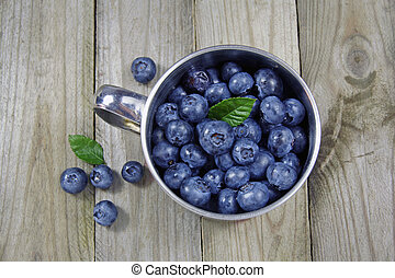 blueberries in metal cup on wooden background