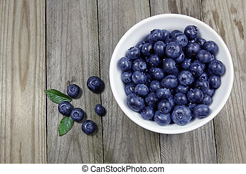 blueberries in porcelain bowl on wooden background