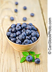 Blueberries in wooden bowl on board