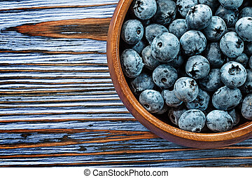Blueberries in wooden bowl on wood board