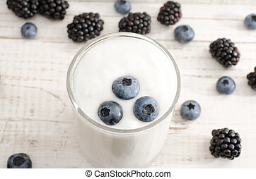 Blueberries in yogurt, berries on the table, light wood background