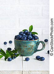 Blueberries with leaves in a ceramic cup on the table