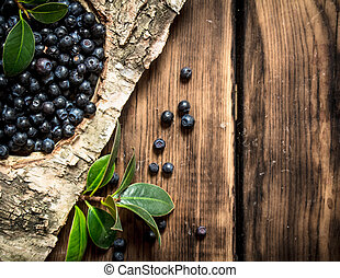 Blueberries with leaves . On wooden background.