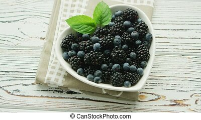 Blueberry and blackberry in bowl - From above blueberry and...
