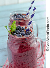 2 Mason jars filled with blueberry and blackberry fresh fruit smoothie sitting on blue wood background with straws and heart napkin