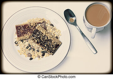 Blueberry and Strawberry Granola Bars stacked in pile of oats and nuts. Coffee with cream. Vintage style photograph.
