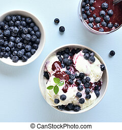 Blueberry ice cream in bowl on blue stone background. Top view, flat lay
