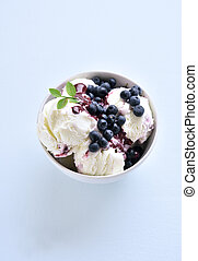 Blueberry ice cream in bowl on blue stone background with free space