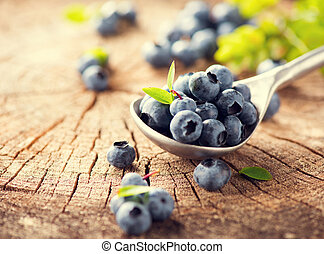 Blueberry in spoon on cracked wooden background. Ripe and...