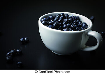 Blueberry in white cup on the black background