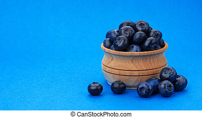 Blueberry isolated on blue background with copy space. A pile of fresh blueberries in a wooden bowl