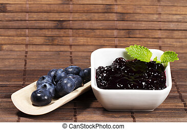 blueberry jam and blueberries on a shovel on wooden background