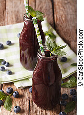 blueberry juice decorated with mint in a glass bottle close-up on the table.