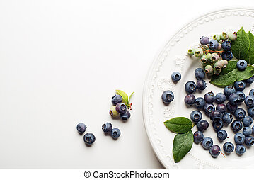 Blueberry - Juicy and fresh blueberries with green leaves on...