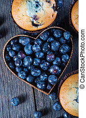 Blueberry muffins and fruit heart on wooden table from above