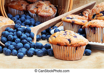 Delicious homemade blueberry muffins with fresh blueberries spilling from a wooden spoon and wicker basket.