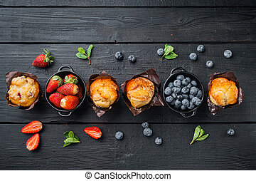 Blueberry muffins, on black wooden table background, top view flat lay with copy space for text
