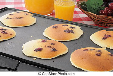 Blueberry pancakes on the grill - Blueberry hotcakes being ...
