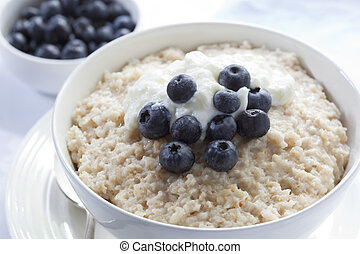 Bowl of oatmeal porridge, topped with fresh blueberries and yogurt. Healthy, delicious variation of a traditional Scottish breakfast.