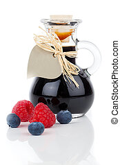 blueberry - raspberry syrup in glass bottle or mixture, with heart label. on white background.