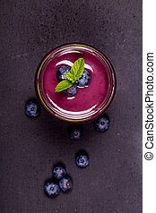 Blueberry smoothie in a glass jar with fresh berries and mint garnish, on a chalk board background