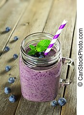 Blueberry smoothie with mint in mason jar with straw against wood
