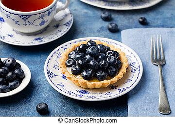 Blueberry tartlet, pie, tart with vanilla custard. Blue stone background