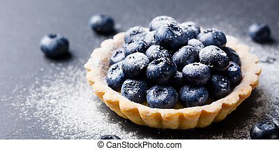 Blueberry tartlet, pie, tart with vanilla custard. Slate stone background.