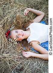 Blueeyed happy smiling teenage girl in wreath relaxing on hay