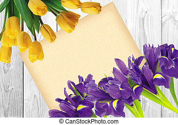 Blueflag or iris flower and yellow tulips with greeting card on white wooden background