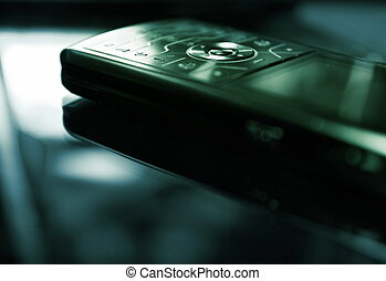 Blue/green toned picture of a mobile phone (shallow DoF, focused on round central button)