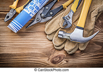 Blueprint protective gloves claw hammer gripping tongs tin snips adjustable spanner on wooden board.
