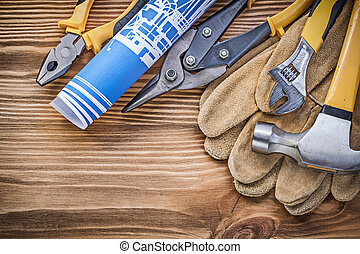 Blueprint safety gloves claw hammer gripping tongs tin snips adjustable wrench on wooden board.