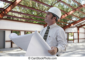 Blueprints & Steel Beams - A construction inspector holding...
