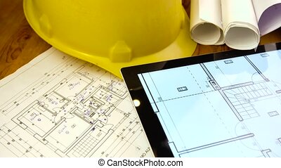 blueprints, tablet and other stuff on table