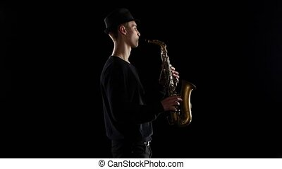 Blues in the performance young musician saxophonist. Black background studio
