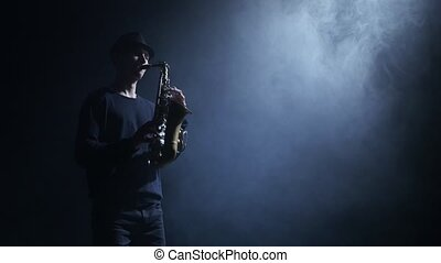 Bluesman performing compositions on the saxophone. Smoke in the dark