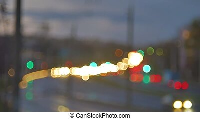 blur background. Moving bokeh circles of night traffic. Defocused night traffic lights Through the glass in drops of rain. Colorful, blurred, bokeh lights background.