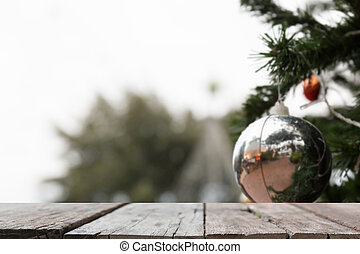 blur background of silver shiny christmas ornament hanging from a green pine tree with selected focus empty wood table for display or montage your product
