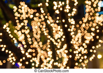 Blur - bokeh Decorative outdoor string lights hanging on tree in the garden at night time
