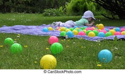 Blur cute baby girl have fun between colorful balls on plaid...