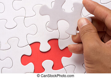 Blur image of close up of hand placing the last jigsaw puzzle piece