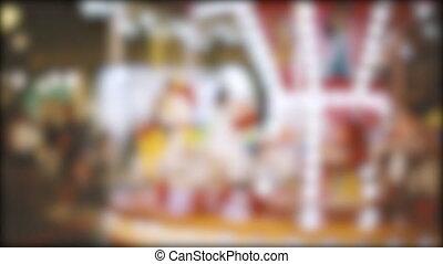 Blur kid playing on Carousel and bokeh of light at night. -...