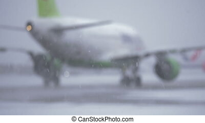 Defocused shot of airliner driving to parking after landing at the airport, view on snowy winter day