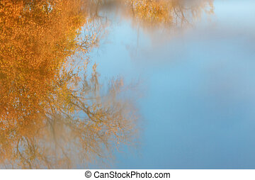 blur reflection in the lake of sky and autumn trees