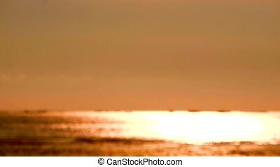 blur reflection orange color of sun light on sea surface and little wave moving