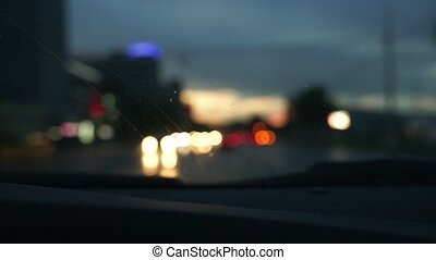 blur shot of woman driving car in the evening in rain