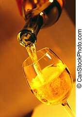 pouring white wine into a glass; taken by a long shutter time with flash;
